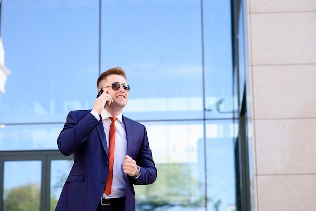 Empresário bem sucedido, falando ao telefone e sorrindo.