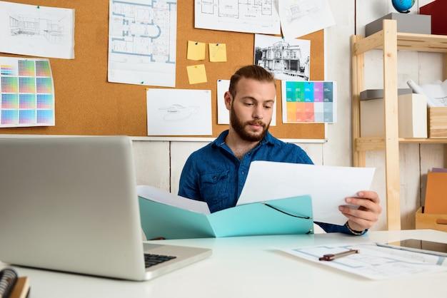 Empresário bem sucedido, olhando através de papéis, sentado no local de trabalho com computador portátil