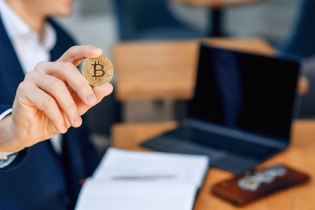 Empresário bem sucedido tem uma moeda de bitcoin de ouro na mão