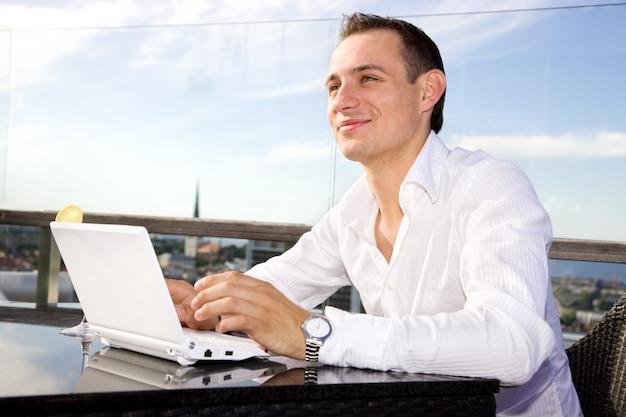 Empresário bonitão em lazer com laptop