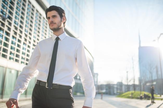 Empresário bonito andando em um ambiente de negócios