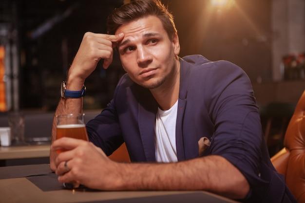 Empresário bonito bebendo cerveja no pub, olhando para longe, pensativo
