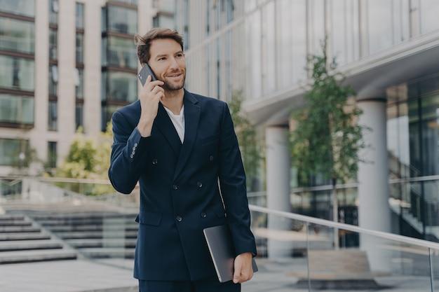 Empresário bonito com a barba por fazer se comunica à distância com colegas ou parceiros