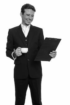 Empresário bonito com barba por fazer em terno isolado contra uma parede branca em preto e branco