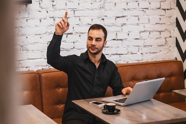 Empresário bonito com laptop chamando garçom enquanto está sentado no café urbano durante a pausa para o café