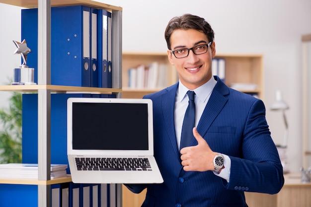 Empresário bonito com laptop no escritório