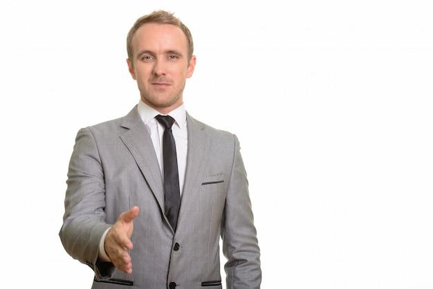 Empresário bonito dando aperto de mão isolado contra parede branca