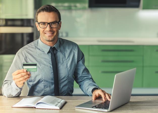 Empresário bonito de óculos está usando um laptop.