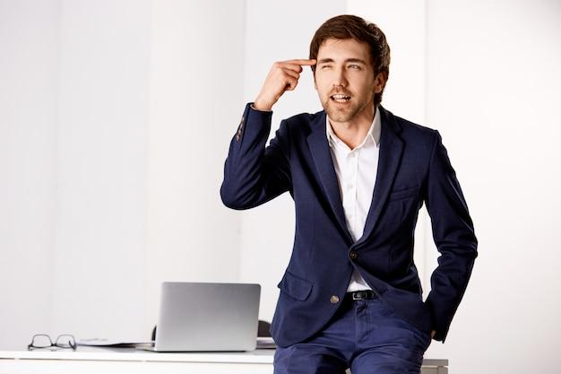 Empresário bonito e desapontado, irritado, repreendendo o empregado por ser irracional, bater a cabeça e apertar os olhos enquanto olha para o outro lado