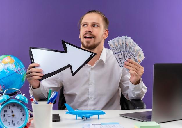 Empresário bonito em camisa branca segurando uma seta branca mostrando dinheiro olhando para o lado com um sorriso no rosto sentado à mesa em escritório sobre fundo roxo