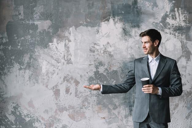 Empresário bonito em pé contra parede resistida, mostrando algo na palma da sua mão