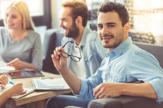 Empresário bonito está segurando óculos