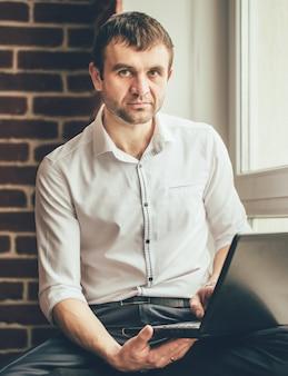 Empresário bonito está sentado atrás do laptop no parapeito da janela de seu escritório.