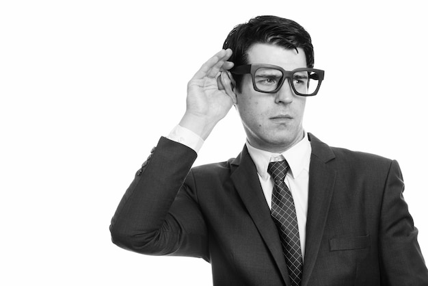 Empresário bonito isolado contra uma parede branca em preto e branco