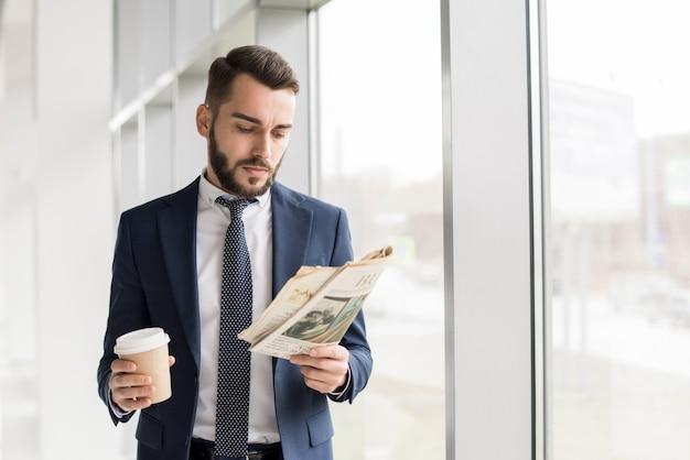 Empresário bonito lendo jornal pela janela