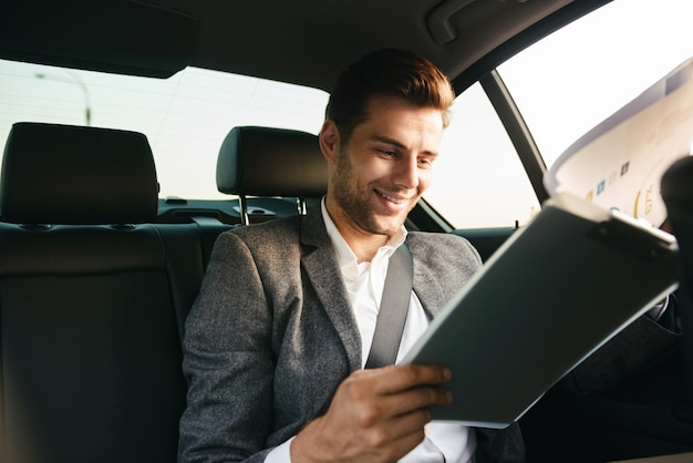 Empresário bonito olhando através de documentos
