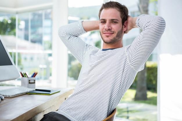 Empresário bonito relaxante na sua cadeira de mesa em um escritório brilhante