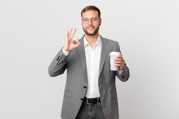 Empresário bonito segurando um café para viagem