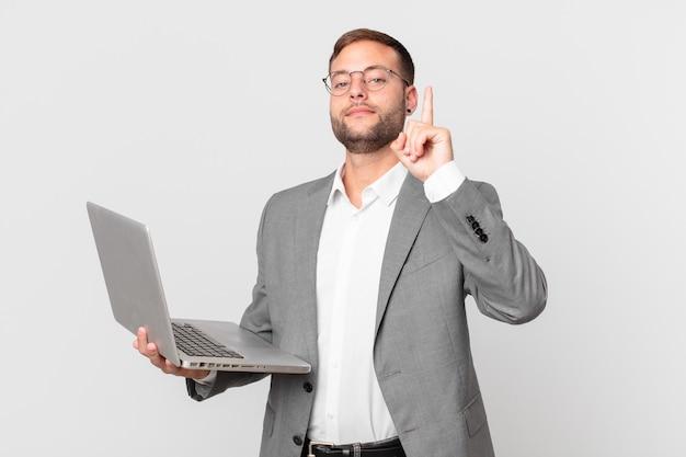 Empresário bonito segurando um laptop