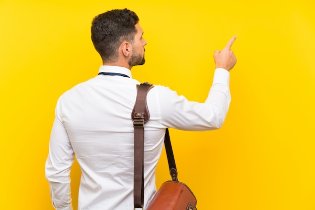 Empresário bonito sobre parede amarela isolada, apontando para trás com o dedo indicador