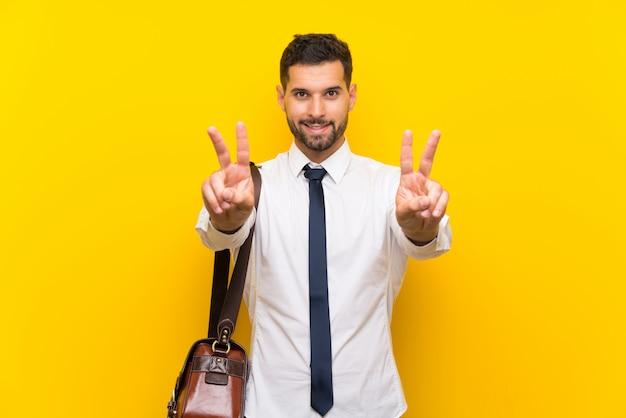 Empresário bonito sobre parede amarela isolada, sorrindo e mostrando sinal de vitória