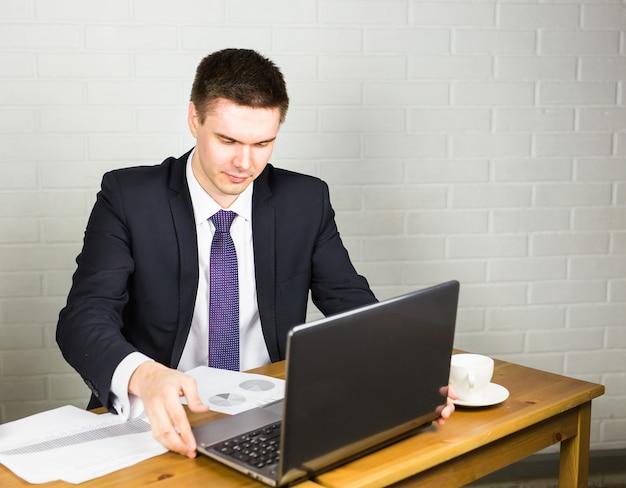 Empresário bonito trabalhando com o laptop no escritório