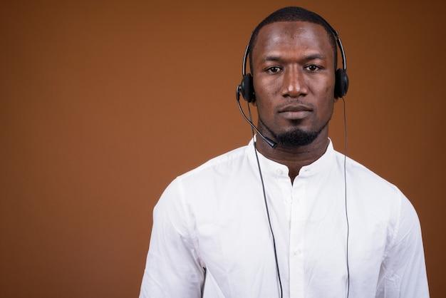 Empresário bonito usando fone de ouvido contra marrom