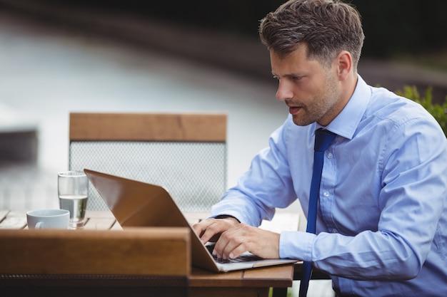 Empresário bonito usando laptop