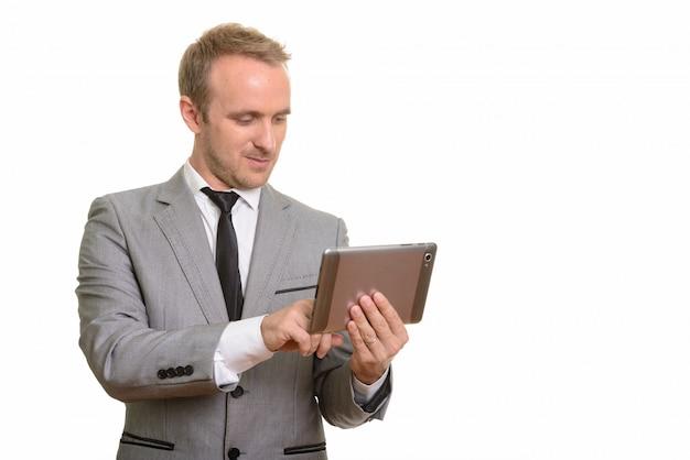 Empresário bonito usando tablet digital isolado contra parede branca