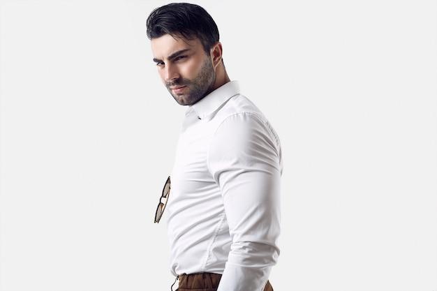 Empresário bronzeado brutal bonito em uma camisa branca e óculos de sol