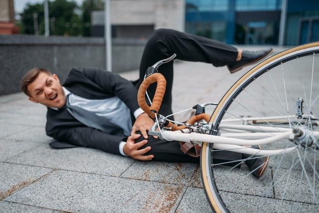 Empresário caiu da bicicleta no prédio de escritórios no centro da cidade. empresário andando em transporte ecológico na rua da cidade