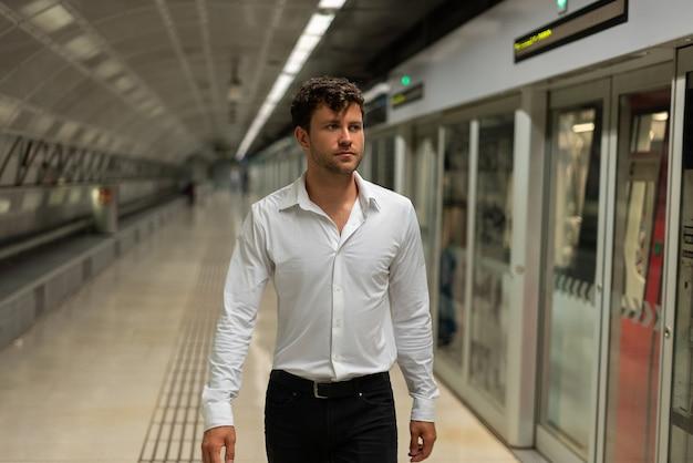 Empresário caminhando na estação de metrô