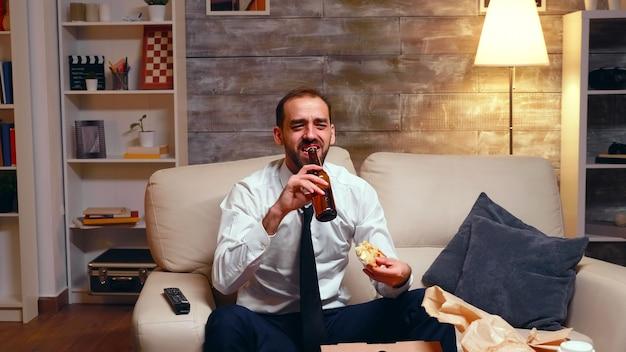 Empresário cansado assistindo tv na sala, bebendo cerveja e comendo fast food.