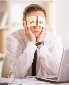 Empresário cansado com nota adesiva em seus olhos.