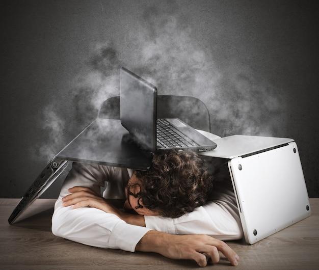 Empresário cansado dormindo embaixo de uma pilha de computadores
