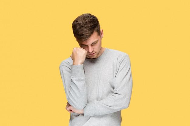 Empresário cansado ou o jovem sério sobre o estúdio amarelo com emoções de dor de cabeça
