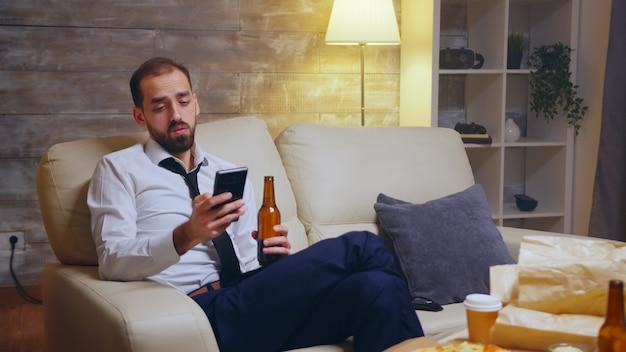 Empresário cansado, sentado no sofá, rolando em seu telefone após um longo dia de trabalho.