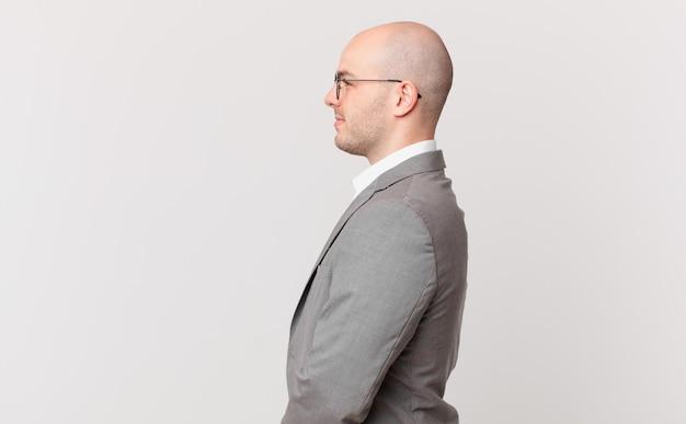 Empresário careca em vista de perfil olhando para copiar o espaço à frente, pensando, imaginando ou sonhando acordado