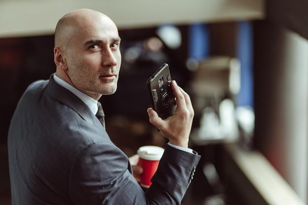 Empresário careca olhando para a câmera virada de costas. homem caucasiano vestindo terno