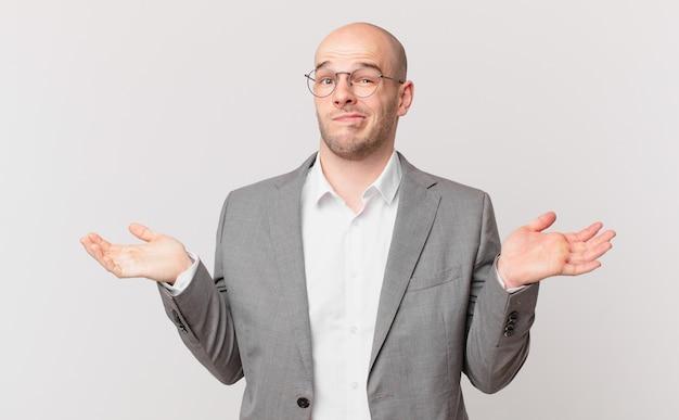 Empresário careca sentindo-se perplexo e confuso, duvidando, ponderando ou escolhendo diferentes opções com expressão engraçada