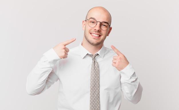 Empresário careca sorrindo com confiança apontando para o próprio sorriso largo, atitude positiva, relaxada e satisfeita