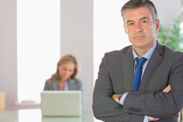 Empresário carrancudo, olhando para a câmera cruzou os braços com uma empresária trabalhando no fundo
