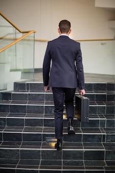 Empresário carregando maleta subindo degraus