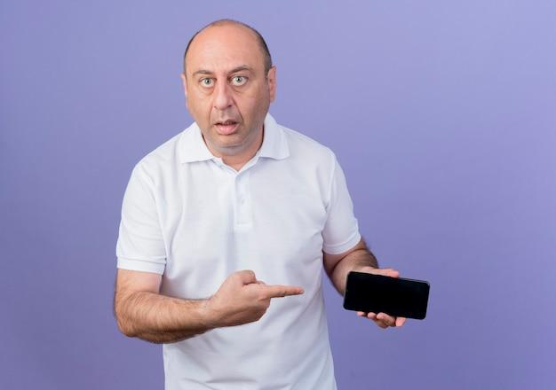 Empresário casual maduro impressionado segurando e apontando para o telefone celular isolado no fundo roxo