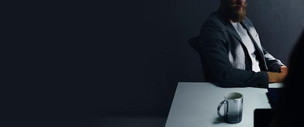 Empresário casual sentado no escuro