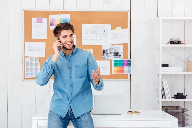 Empresário casual sorridente, sentado na mesa do escritório e falando no celular