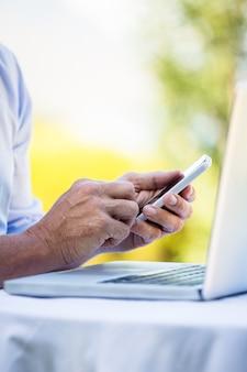 Empresário casual usando laptop e smartphone