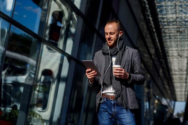 Empresário caucasiano atraente, vestindo roupas casuais, caminhando lá fora, detém o computador tablet e bebe café perto do centro de escritório moderno. conceito de negócios.