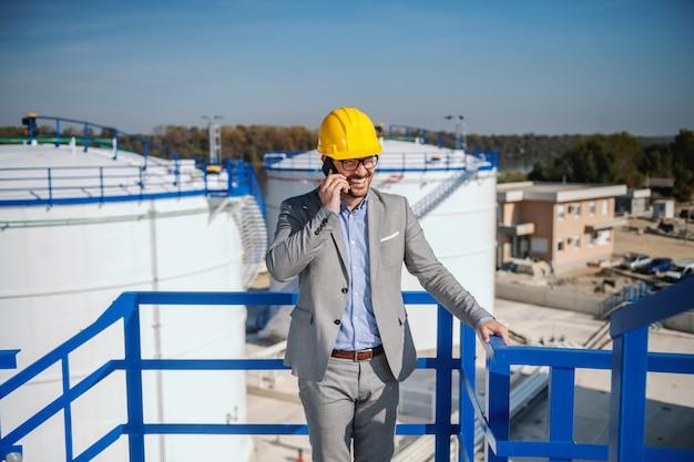 Empresário caucasiano bonito de terno e com o capacete na cabeça, falando ao telefone em pé ao ar livre. no fundo estão o armazenamento do tanque de óleo.