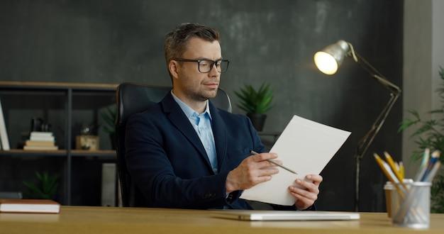 Empresário caucasiano bonito em copos, sentado à mesa no escritório e verificar documentos com lápis nas mãos.